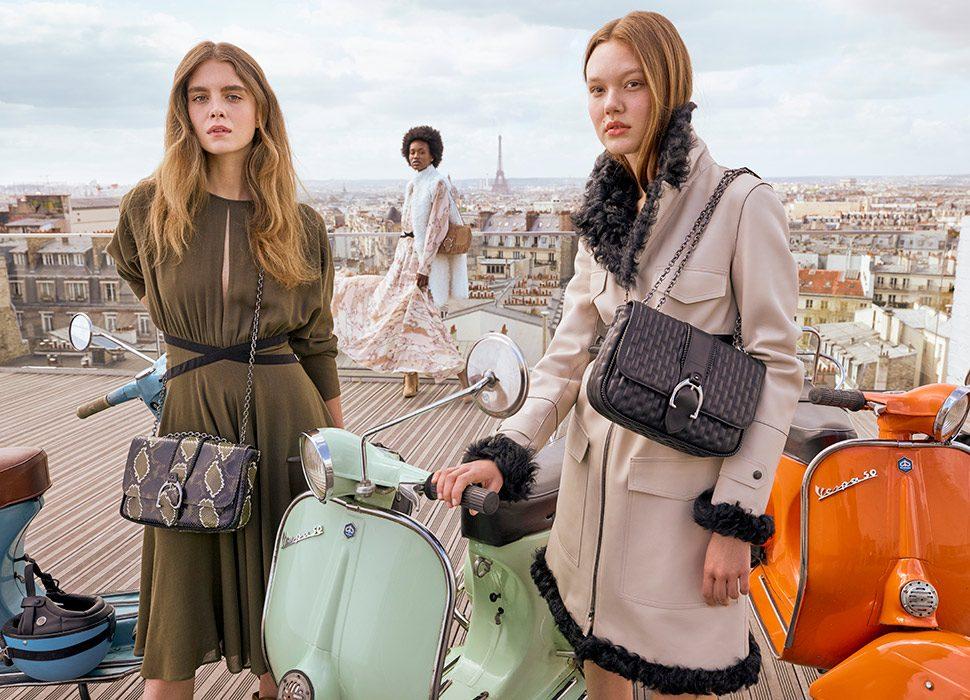 Women pose with leather Longchamp purses.