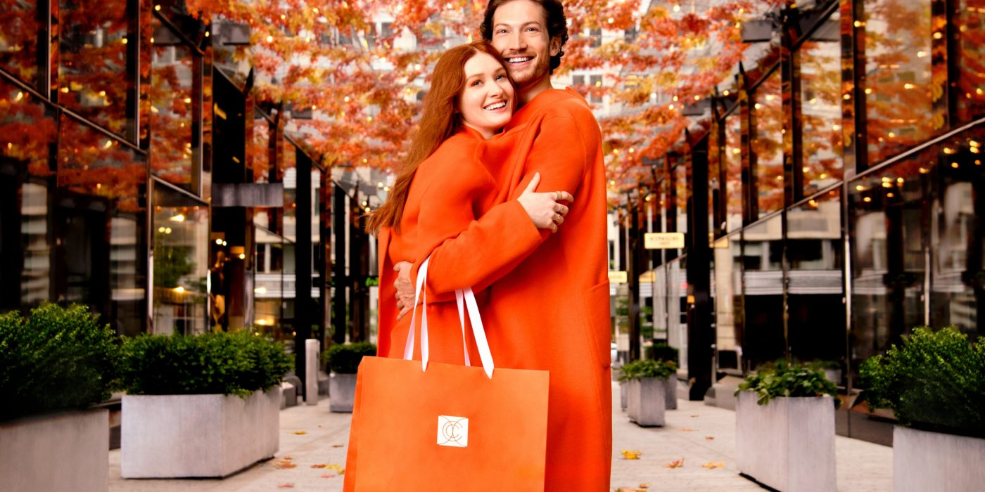 A man and woman share an orange coat in Palmer Alley at CityCenterDC