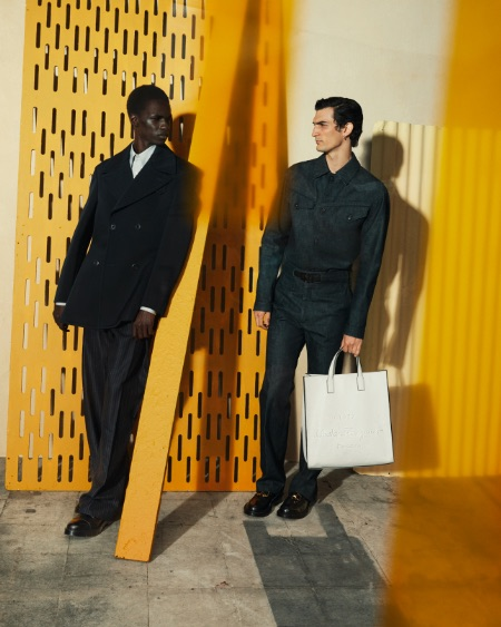 Two men wear dark shirts and pants by Salvatore Ferragamo