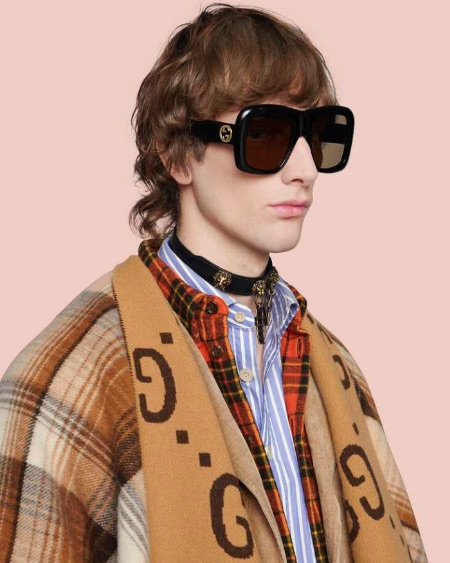 A man wears large sunglasses, plaid shirts, and a wool poncho, all by Gucci