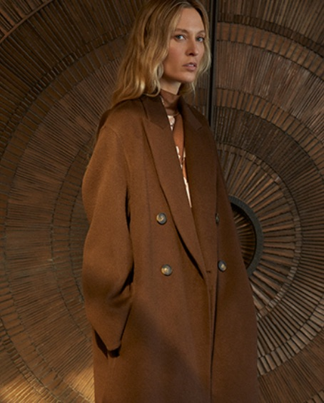 A woman wears a long brown double-breasted overcoat by Vince