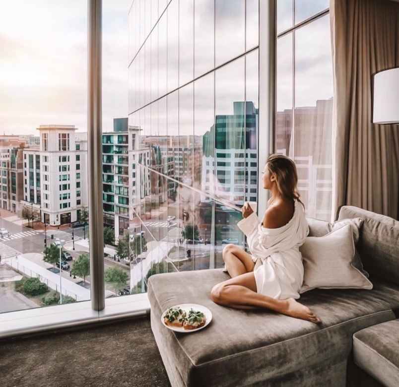 A woman enjoys the view from her room at Conrad Washington D.C.