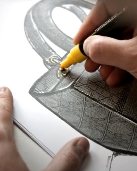 An artist sketches a Dior leather handbag