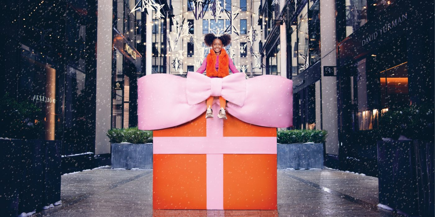 A girl sits on a giant holiday gift.