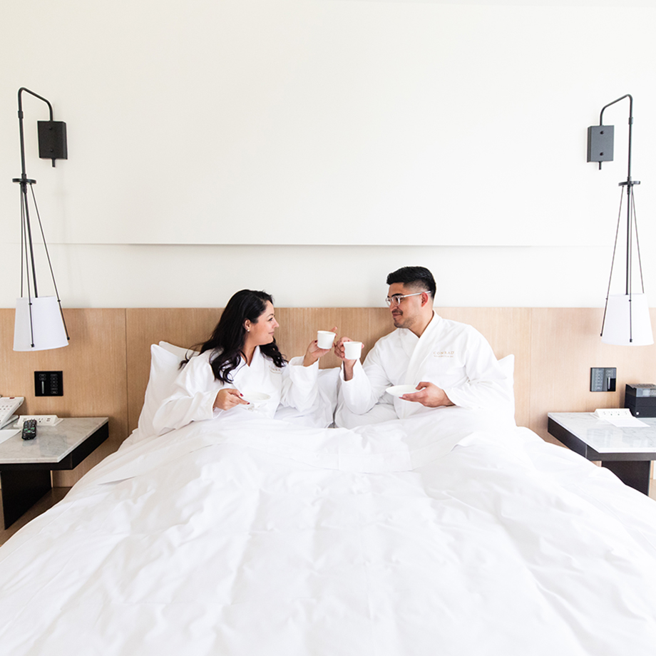 A couple drinks coffee in bed at the Conrad Hotel at CityCenterDC