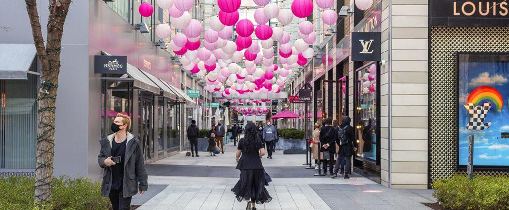 Pedestrians walk beneath pink lanterns at CityCenterDC's Palmer Alley