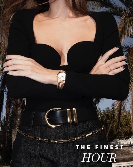 A woman wearing a black shirt models a gold Breitling watch