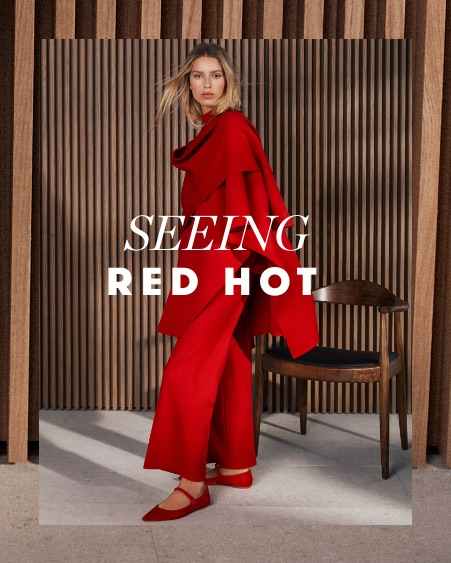 A woman wearing a striking red suit by Carolina Herrera