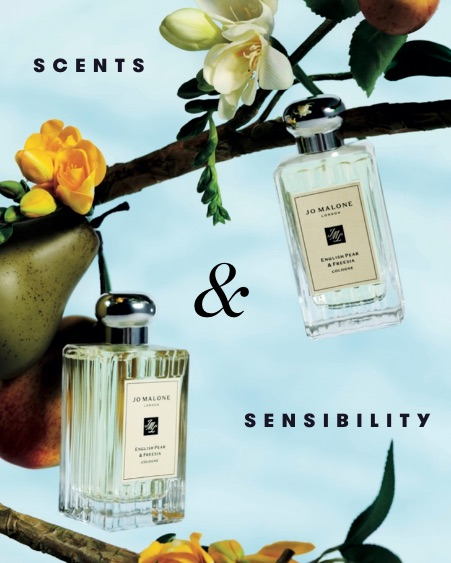 Two glass bottles of Jo Malone fragrance hang from a tree branch amongst flowers