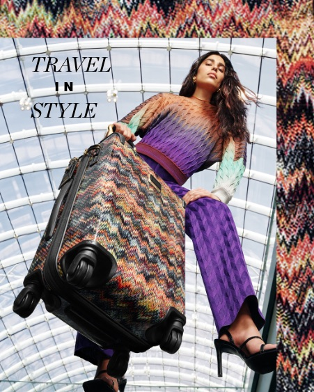 A woman holding a patterned Tumi hard shell suitcase